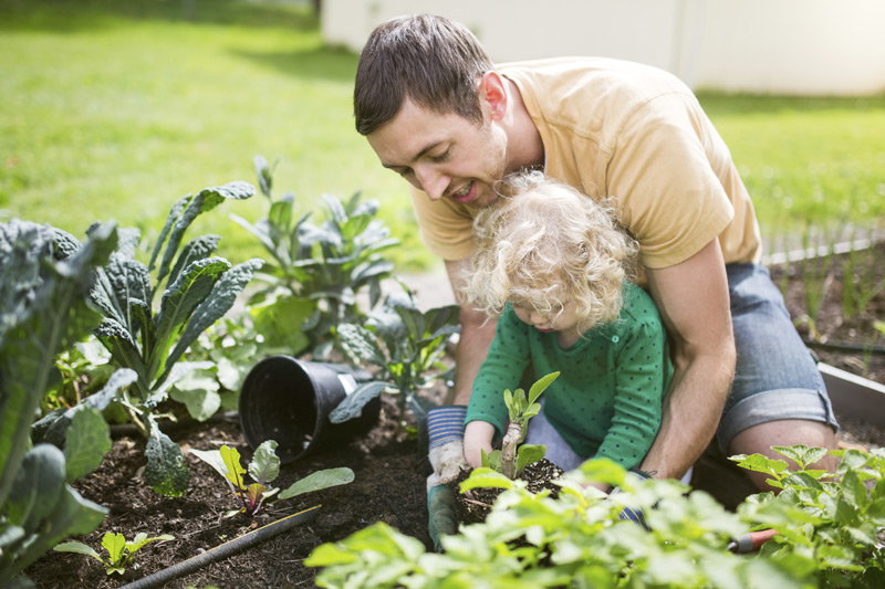 image of father gardening with young daughter